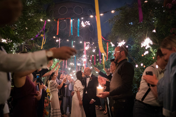 bride, groom and wedding guests celebrating in the night outside